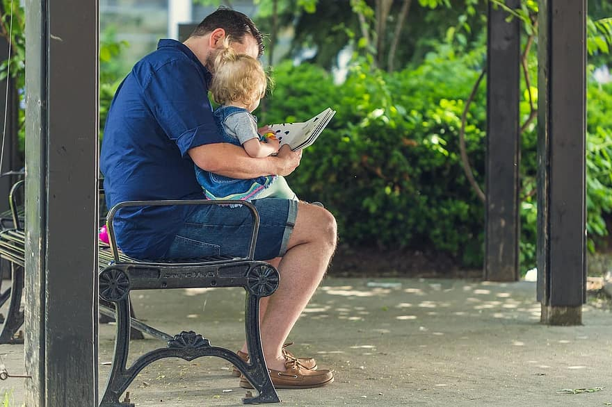 people father man reading book baby girl kid child