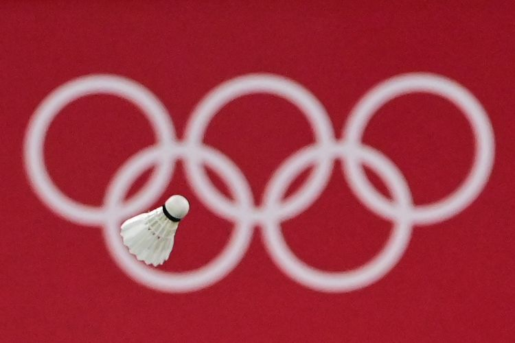 A shuttlecock flies in front of the Olympic rings logo during the women's singles badminton round of 16 match between Japan's Akane Yamaguchi and South Korea's Kim Ga-eun during the Tokyo 2020 Olympic Games at the Musashino Forest Sports Plaza in Tokyo on July 29, 2021. (Photo by Pedro PARDO / AFP)