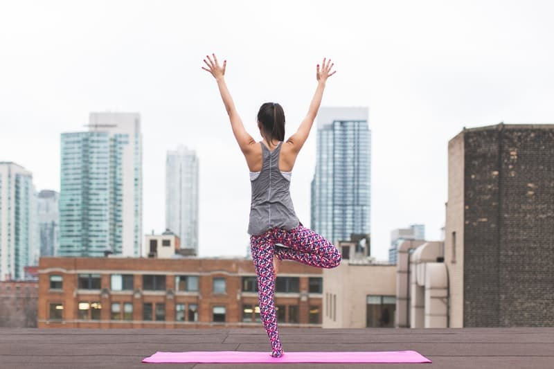 girl doing yoga on the rooftop of a skyscraper in new york city