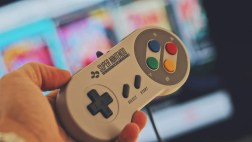 person-holding-white-snes-controller