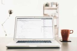 Macbook pro standing on top of a modern workspace desk