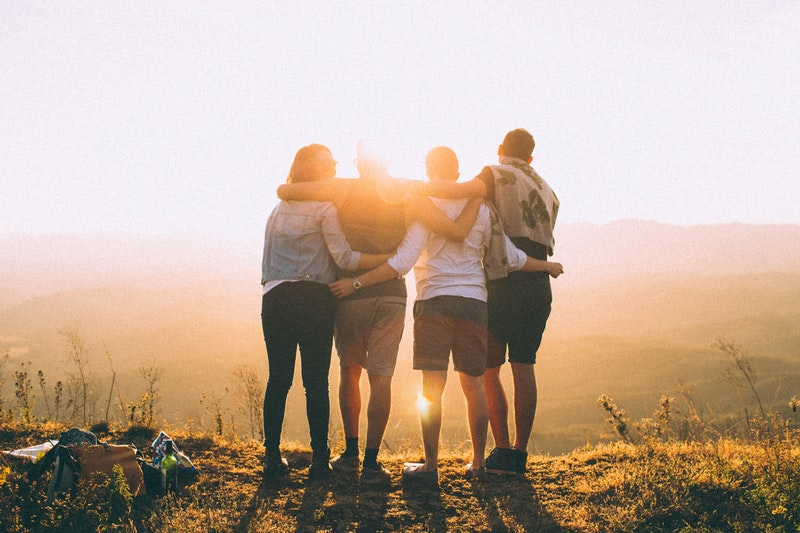 four friends watching the sunset together from a tall mountain