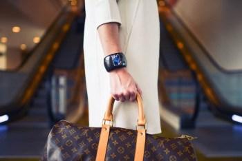 young woman holding louis vuitton duffle bag