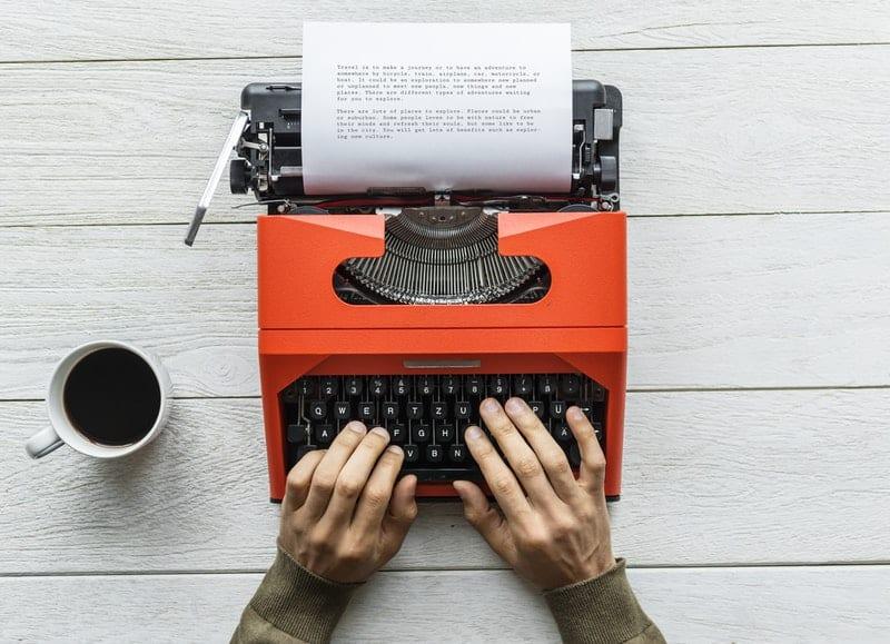 person typing on a vintage black and orange typewriter
