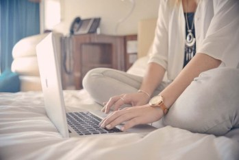 woman typing on her laptop while sitting on the bed