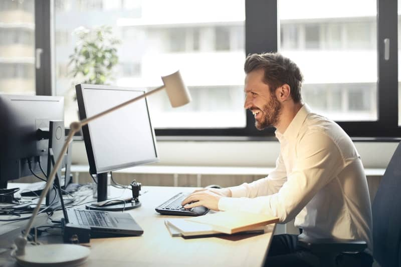 man-in-white-dress-shirt-sitting-on-black-rolling-chair-while-facing-black-computer-set-and-smiling