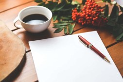 Blank paper with pen and coffee cup on wooden table