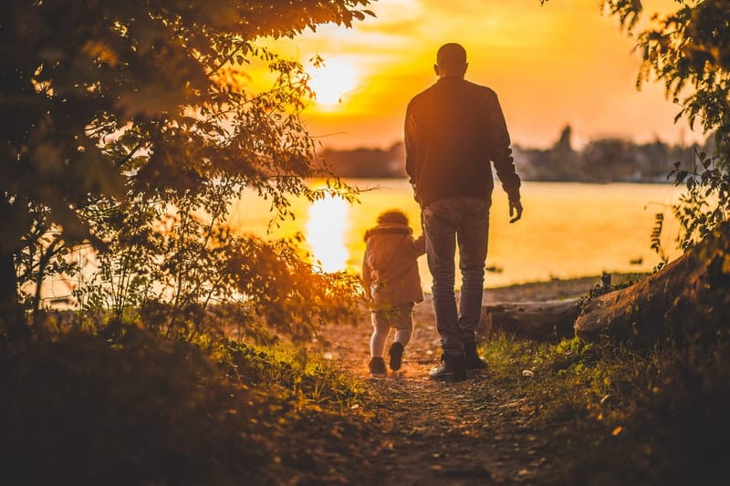 father and son walking into the sunset