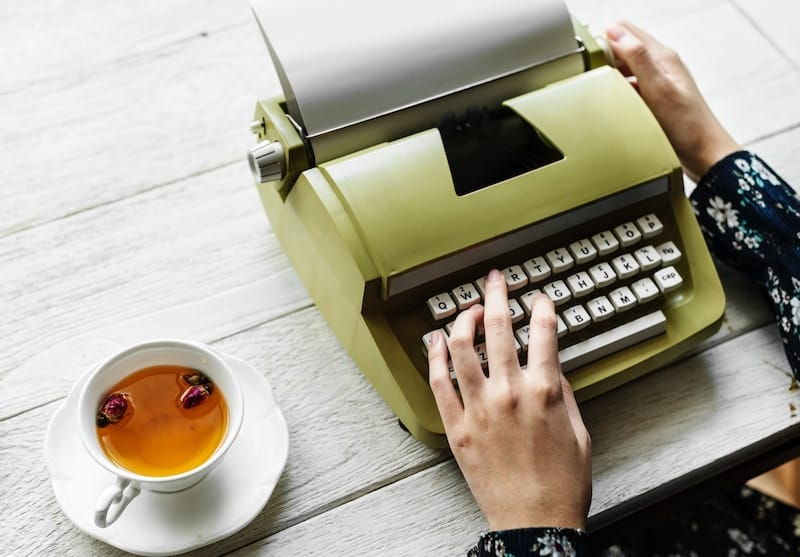 Person writing on her vintage typewriter