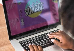 Woman creating a brochure on a macbook pro-min