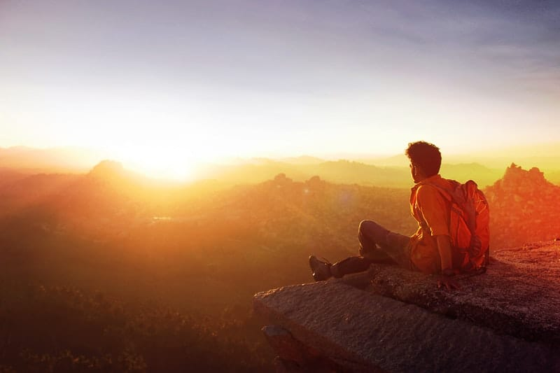 man sitting on the edge of a rock watching the sunrise