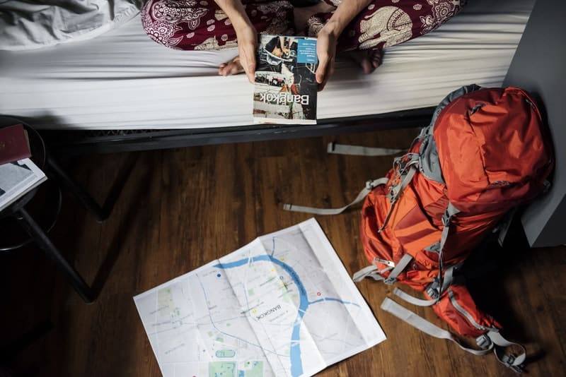 backpacker staying inside a hostel reading lonely planet guide book about bangkok thailand