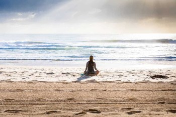 Woman Meditating Early in the Morning by the beach