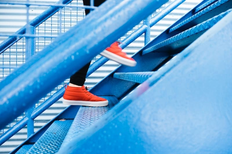 Woman with red shoes going up blue stairs