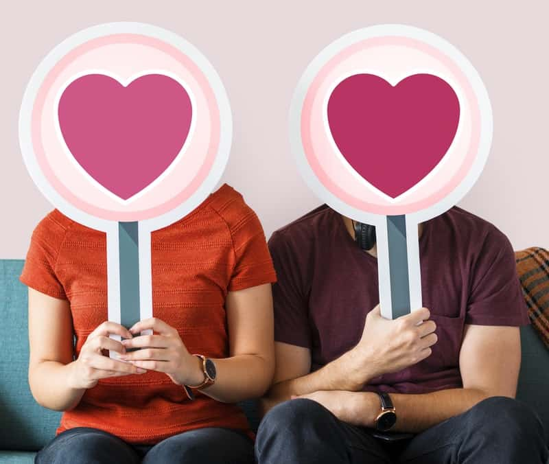 man-and-woman-holding-heart-boards