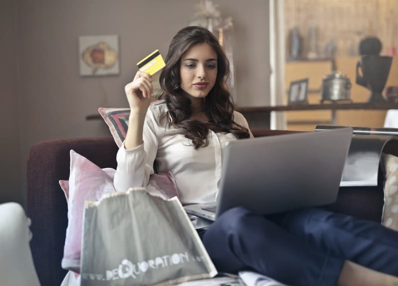young woman holding her credit card while shopping online