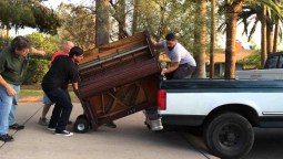 Four men moving a piano