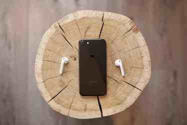 Iphone 7 and apple air pods laying on a wooden chair