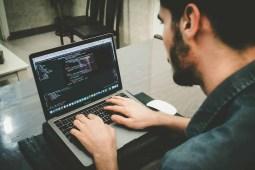 Man writing code on his laptop