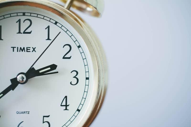 round Timex analog clock at 2-33