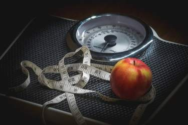 weight-check-dveice-with-measuring-tape-and-apple