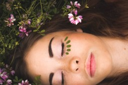 Beautiful Young Woman Laying in a Flower Field