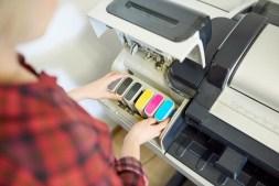 crop-woman-putting-ink-in-printer