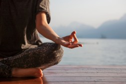 Woman practicing yoga by a lake