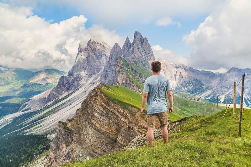 Homme de dos face aux crêtes montagneuses