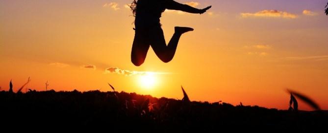 silhouette de femme au crépuscule faisant un bon de joie et de liberté