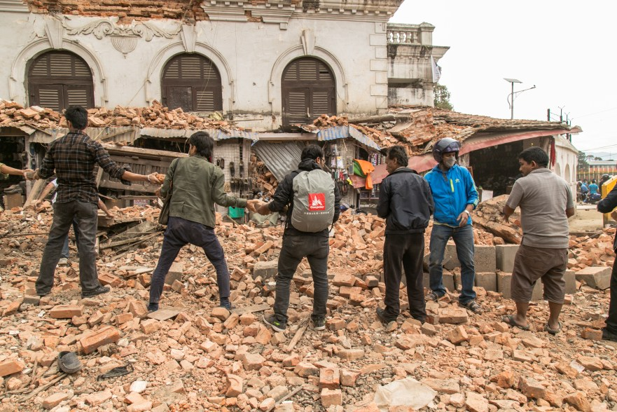 Passersby relay bricks to a pile in the search for injured or dead people in the rubble of a fallen building in central Kathmandu, an hour after the April 25 earthquake.