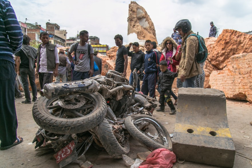 A group of people look at a motorcycle that has been smashed and twisted by the fallen Dharahara tower in Kathmandu. The remains of the tower stand in the background, littered with bricks and large chunks of the building.