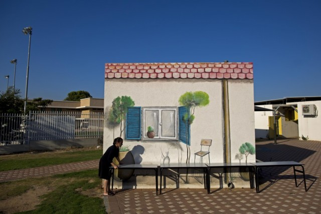 An Israeli girl places tables next to a concrete protective shelter painted by Israeli artist Eliasaf Myara in the city of Sderot, located a few kilometers from the border with the Gaza Strip, Israel, 17 June 2015. The Israeli Defense Ministry has placed hundreds of small concrete protective shelters to all towns located near the Gaza Strip to protect its citizens from incoming rockets. On 08 July 2015, Israel will mark one year since the 2014 Israel–Gaza conflict, also known as Operation Protective Edge.