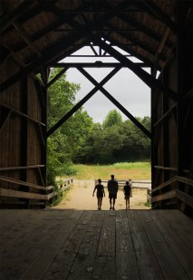 Family Walking Through The Wooden Covered Bridge In Felton, California