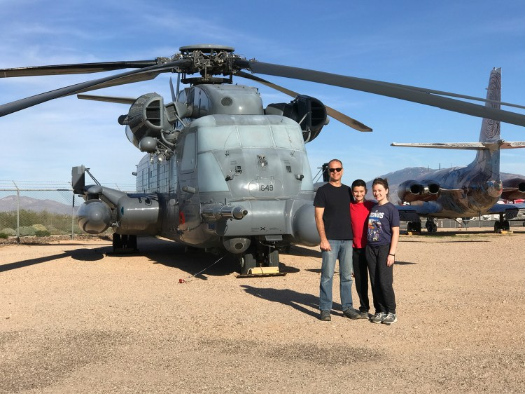 Brian, Natalie, and Carter Bourn standing in front of a military helicopter