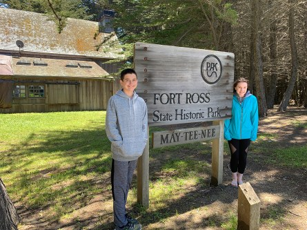 Carter and Natalie Standing By The Fort Ross State Historic Park Sign