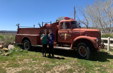 Natalie and Carter Standing In Front of A Vintage Fire Truck