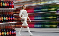 "A model presents a creation by German designer Karl Lagerfeld as part of his Fall/Winter 2014-2015 women's ready-to-wear collection for French fashion house Chanel at the Grand Palais transformed into a ""Chanel Shopping Center"" during Paris Fashion Week"