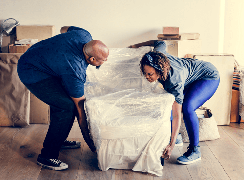 husband and wife moving furniture image