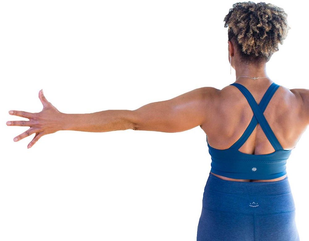 yoga student facing away arms out left side