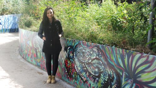 Karis Knight by her section of the mural, an adder