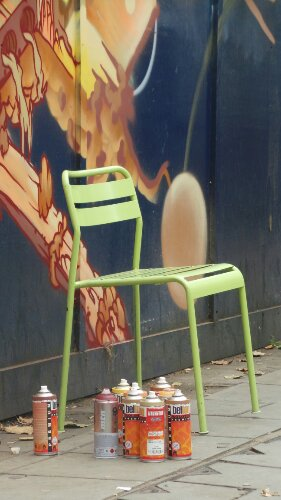A green chair and orange paint
