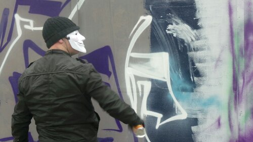 Solo One wore a V for Vendetta mask to obscure his identity whilst painting