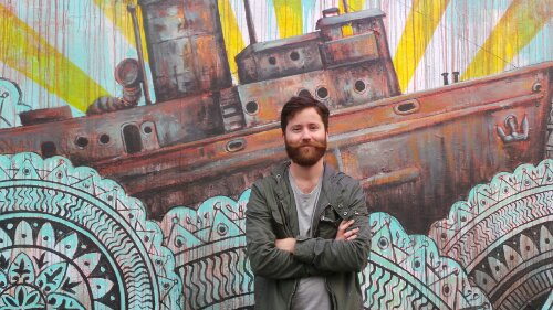 New York's Beau Stanton by his mural on Pedley Street