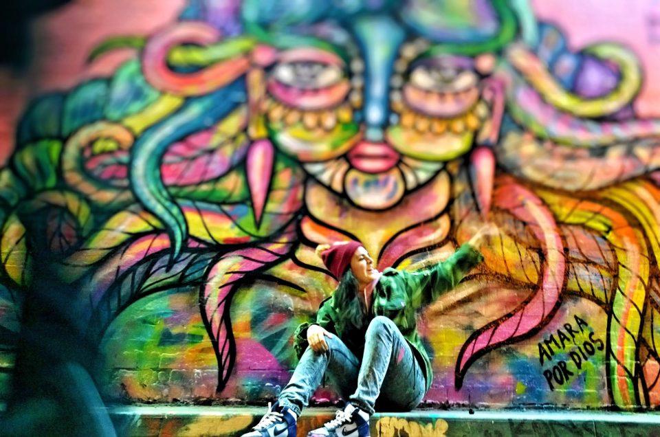 Amara next to her mural from Femme Fierce