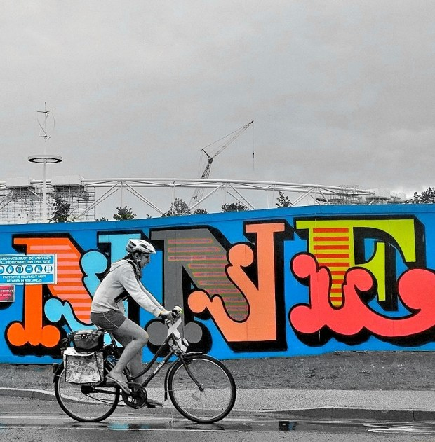 A cyclist cycles past the mural with the Olympic Stadium in the background