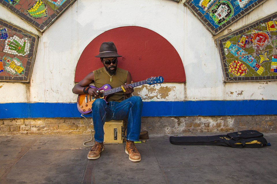 A busker plays underneath a mural made by local school children