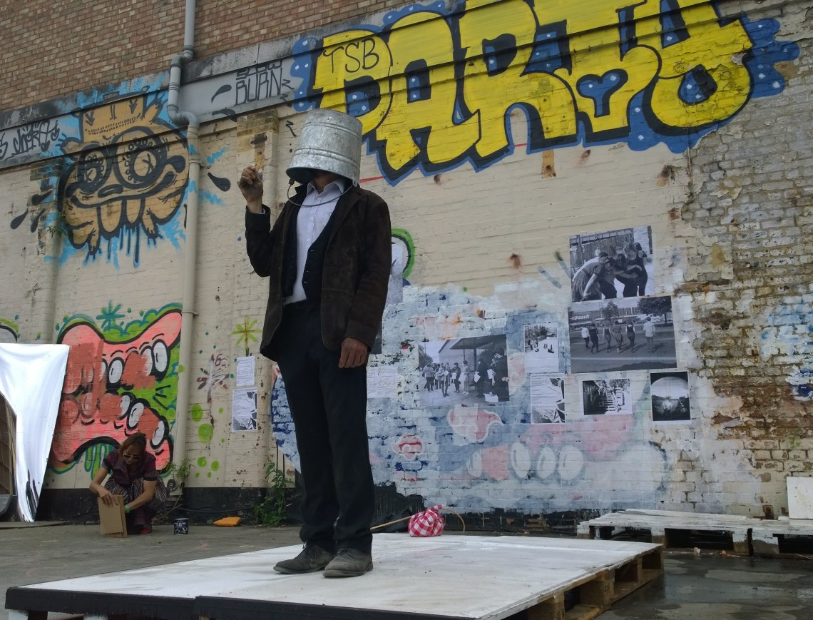 A performance artist stood with a bucket on his head