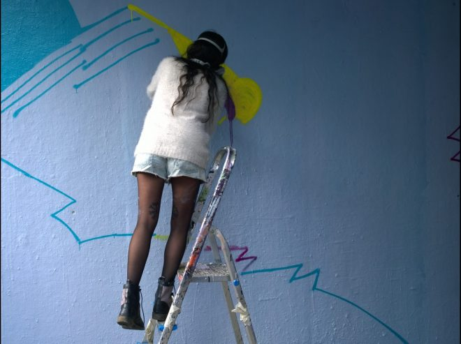 Cleo43 in the middle of creating her colourful abstract piece