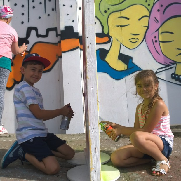 Some young painters of the future putting the finishing touches to one of the signs